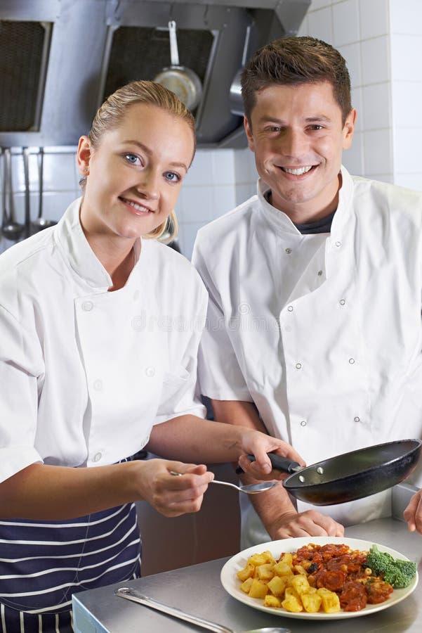 Portret van Chef-kok Instructing Female Trainee in Restaurant Kitche royalty-vrije stock foto