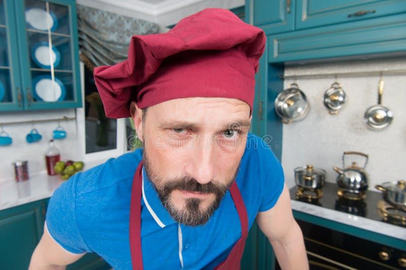 Portret van Chef-kok met verdachte blik Gebaarde chef-kok in hoed Boze mens in schort bij keuken De gebaarde kok met in verwarrin stock foto