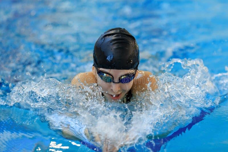 Portret van close-up jong meisje in beschermende brillen en GLB-het zwemmen vlinderslagstijl in de blauwe waterpool stock foto's