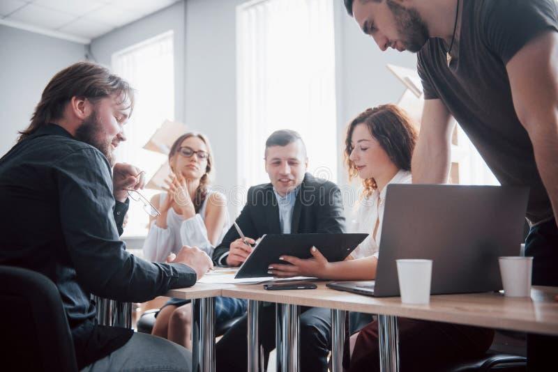 Portret van creatief team die in bureau op vergadering spreken stock foto's