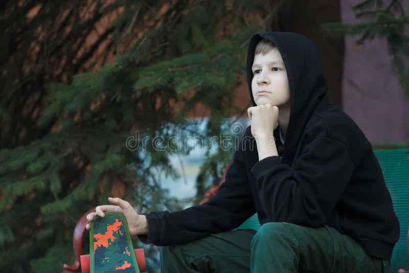 Portret van dagdromen het tienerskateboarder vooruitzien stock foto