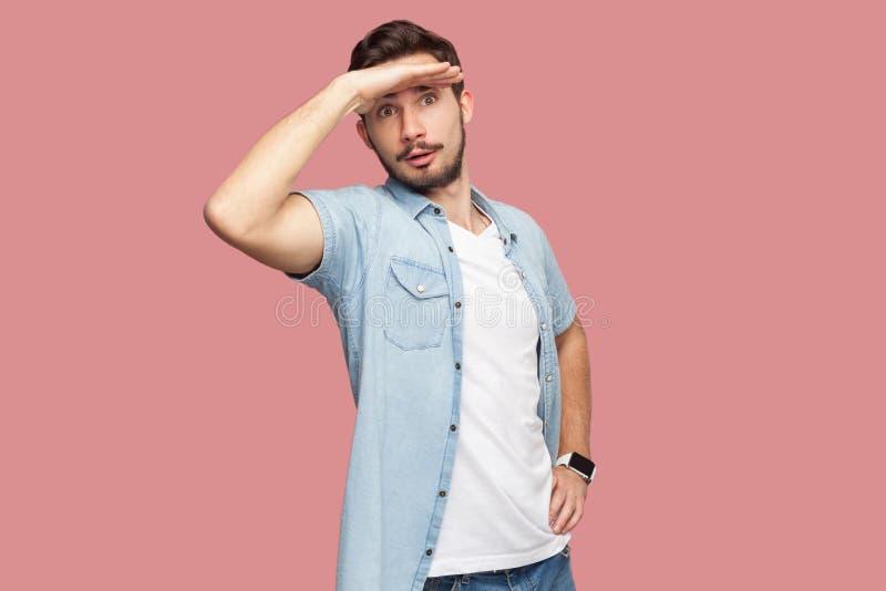 Portret van de aandachtige knappe gebaarde jonge mens in blauw toevallig zich met hand op voorhoofd bevinden en stijloverhemd die stock foto