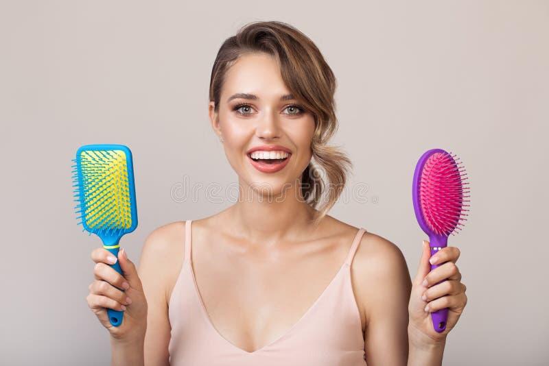 Portret van de aantrekkelijke het glimlachen haarborstels van de vrouwenholding stock afbeelding