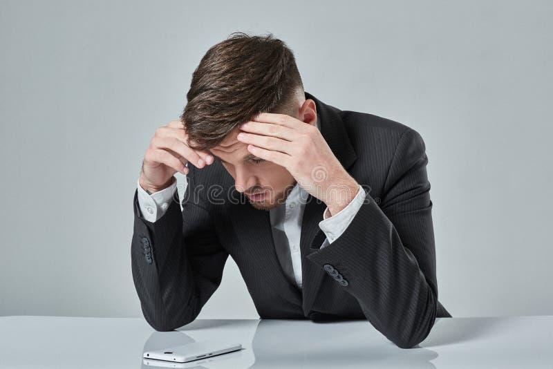 Portret van de aantrekkelijke jonge Kaukasische mens die cellulaire telefoon met behulp van terwijl het zitten bij bureaulijst stock foto