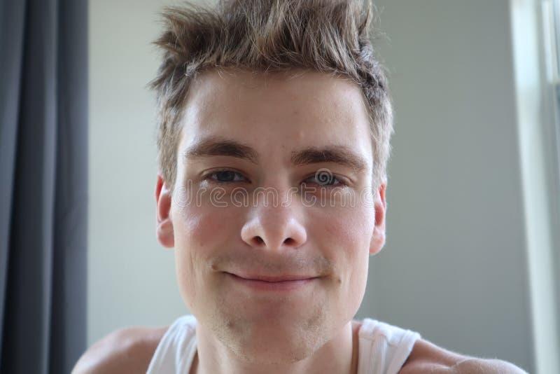 Portret van de aantrekkelijke jonge mens met tevreden uitdrukking Witte achtergrond Emotioneel portret duidelijke huid en kort ha stock afbeelding