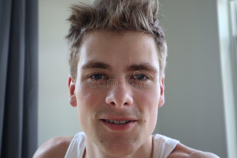 Portret van de aantrekkelijke jonge mens met tevreden uitdrukking Witte achtergrond Emotioneel portret duidelijke huid en kort ha royalty-vrije stock afbeeldingen