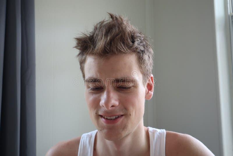Portret van de aantrekkelijke jonge mens met tevreden uitdrukking Witte achtergrond Emotioneel portret duidelijke huid en kort ha royalty-vrije stock afbeelding