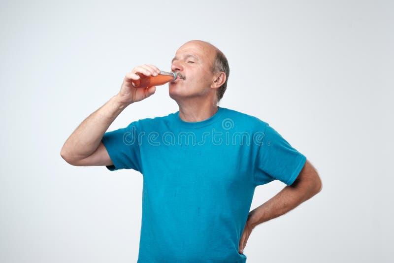 Portret van de aantrekkelijke Kaukasische mens in blauwe t-shirt die en het drinken soda bevinden zich stock afbeelding