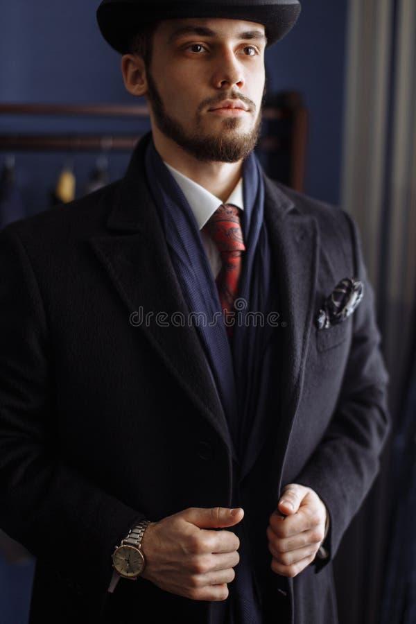 Portret van de aantrekkelijke mens in donkere laag en in kostuum binnen kleermakers royalty-vrije stock foto