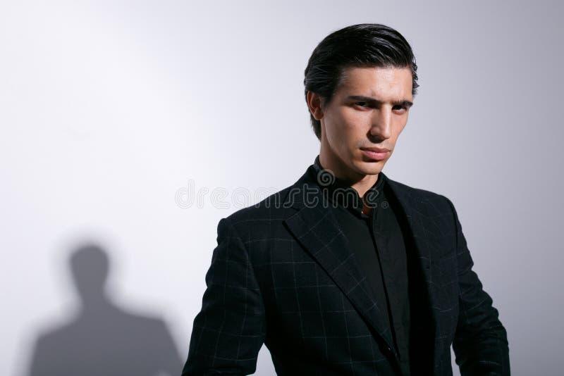 Portret van de aantrekkelijke mens in zwart kostuum, op witte achtergrond Binnen geschoten horizontaal stock fotografie