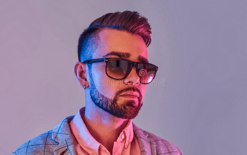 Portret van de aantrekkelijke peinzende mens in checkeretblazer en zonnebril stock foto's