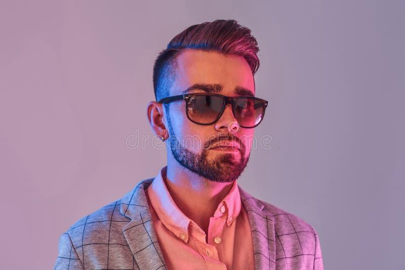 Portret van de aantrekkelijke peinzende mens in checkeretblazer en zonnebril stock afbeeldingen