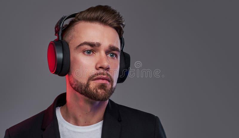 Portret van de aantrekkelijke peinzende mens in draadloze hoofdtelefoons royalty-vrije stock foto's