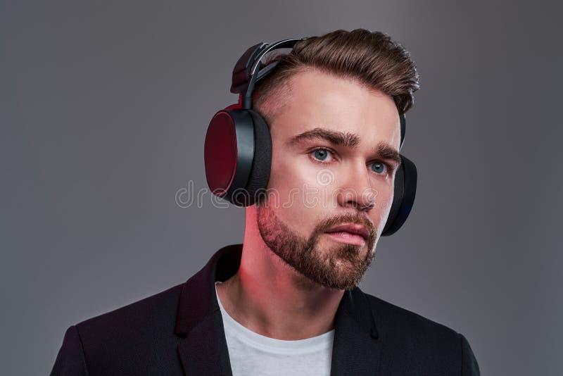 Portret van de aantrekkelijke peinzende mens in draadloze hoofdtelefoons stock foto's