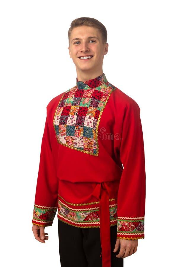 Portret van de aantrekkelijke Russische kerel in rood volksdiekostuum op wit wordt geïsoleerd stock fotografie