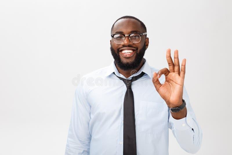 Portret van de Afrikaanse Amerikaanse bedrijfsmens die en o.k. teken glimlachen tonen Kinetisch gedragconcept stock fotografie