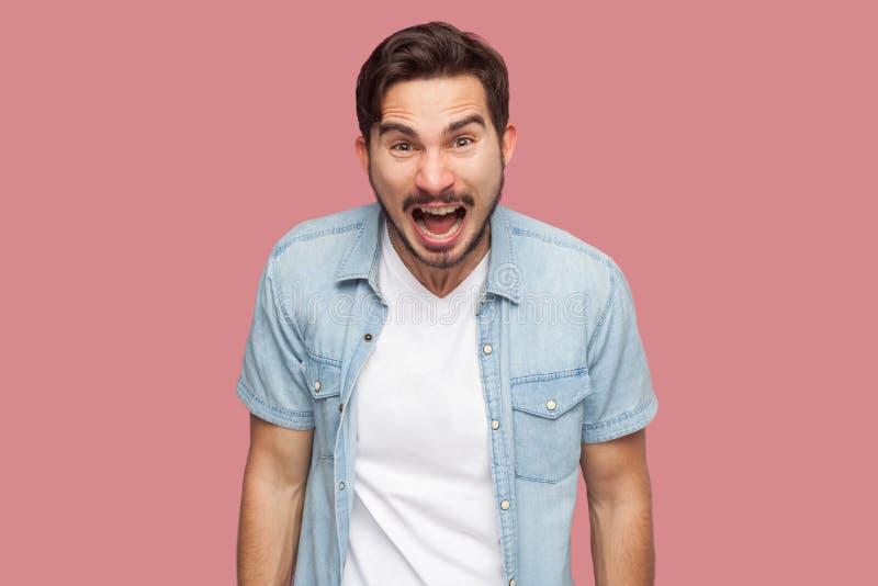Portret van de agressieve geschokte knappe gebaarde jonge mens in blauwe toevallige stijloverhemd status bekijkend en gillend bij stock afbeelding