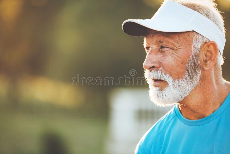 Portret van de atletische rijpe mens na looppas De knappe hogere mens die rusten na stoot bij het park aan royalty-vrije stock foto