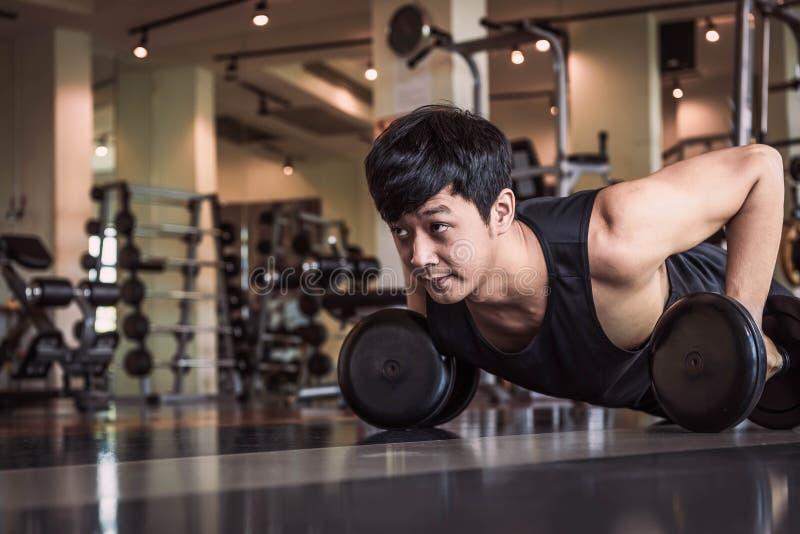 Portret van de Aziatische geschiktheidsmens die verhogend oefening met domoor in gymnastiek doen Mensenlevensstijl en Sportconcep royalty-vrije stock foto