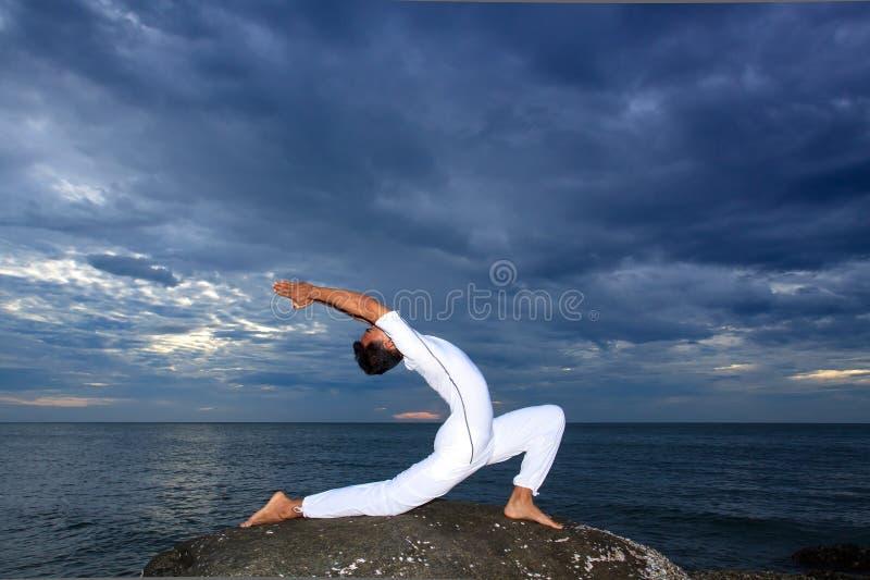 Portret van de Aziatische jonge mens die yoga op steen doet royalty-vrije stock foto