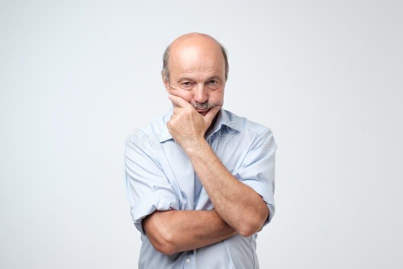 Portret van de bejaarde ernstige man die zijn kin wrijven stock foto's