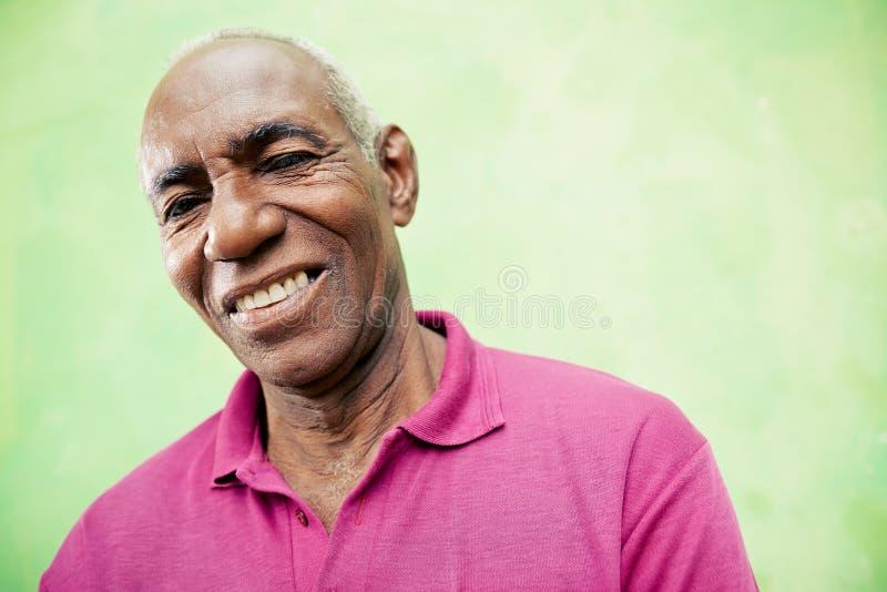 Portret van de bejaarde zwarte mens die en bij camera bekijken glimlachen stock afbeelding