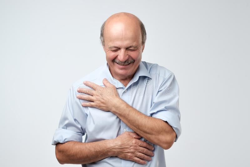 Portret van de blije aantrekkelijke kale mens met snor, lacht hij gelukkig bij grappige verhaal of grap, die in goede stemming zi stock fotografie