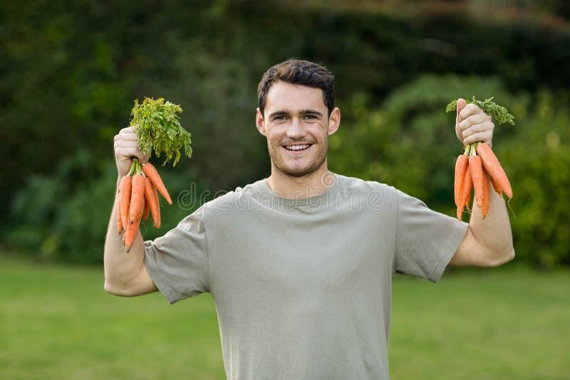Portret van de bos van de jonge mensenholding van wortelen stock afbeelding