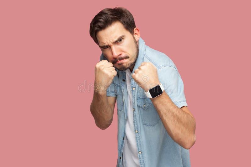 Portret van de boze knappe gebaarde jonge mens in blauw toevallig stijloverhemd die zich met het in dozen doen van vuisten en het stock foto's