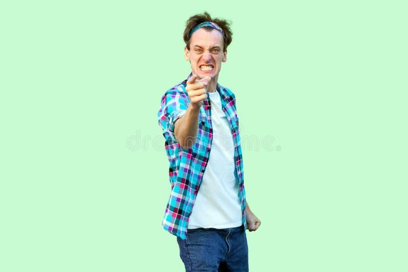 Portret van de boze zenuwachtige jonge mens in toevallig blauw geruit overhemd en hoofdband die, tanden dichtklemmen, en beschuld stock foto