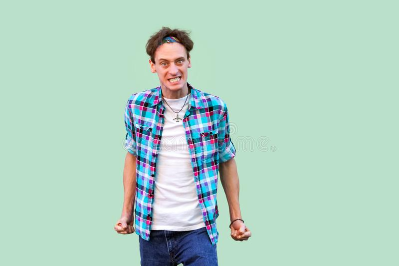 Portret van de boze zenuwachtige jonge mens in toevallige blauwe geruite overhemdshoofdband die, dichtklemmend tanden, die camera stock foto