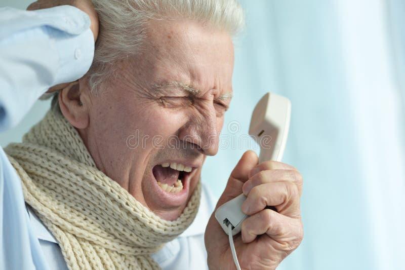Portret van de boze zieke hogere mens die op telefoon gillen stock afbeeldingen
