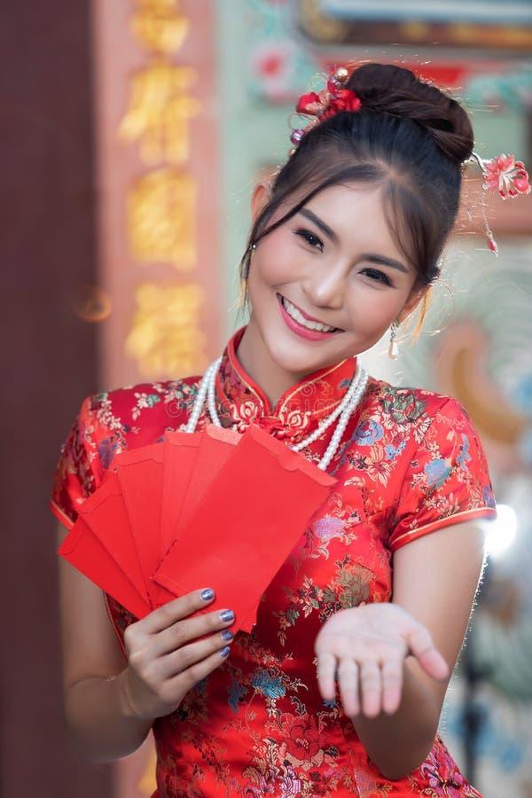 Portret van de Chinese traditionele kleding van de vrouwenslijtage cheongsam en holdings Rode envelop of gife bon voor beloning b stock fotografie