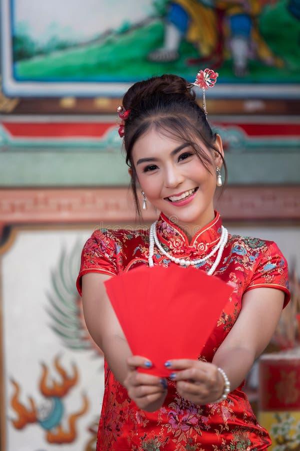 Portret van de Chinese traditionele kleding van de vrouwenslijtage cheongsam en holdings Rode envelop of gife bon voor beloning b royalty-vrije stock foto's