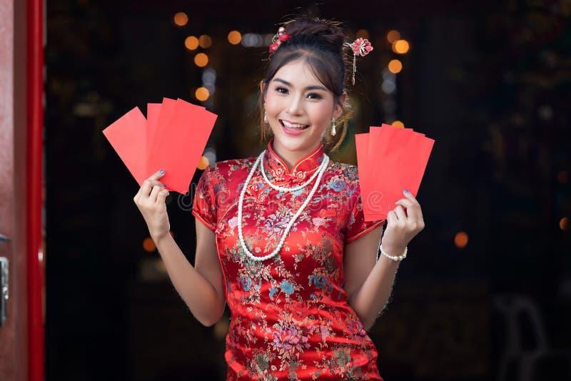 Portret van de Chinese traditionele kleding van de vrouwenslijtage cheongsam en holdings Rode envelop of gife bon voor beloning b stock foto