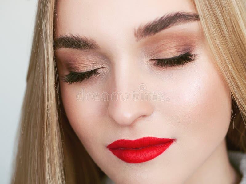 Portret van de close-up het natuurlijke lichte schoonheid van het model van de blondevrouw met de trillende verzadigde rode make- stock afbeelding
