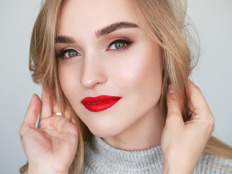 Portret van de close-up het natuurlijke lichte schoonheid van het model van de blondevrouw met de trillende verzadigde rode make- stock fotografie