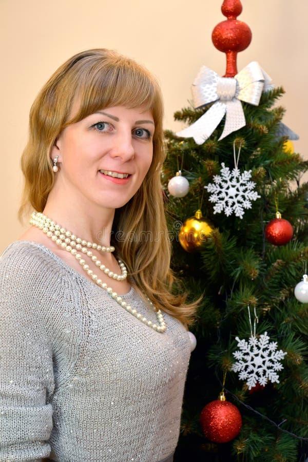 Portret van de dertig-jaar-oude vrouw over een Nieuwjaarboom royalty-vrije stock afbeelding
