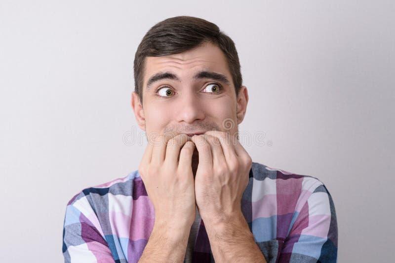 Portret van de doen schrikken mens die zijn die spijkers bijten op grijze achtergrond wordt geïsoleerd stock fotografie