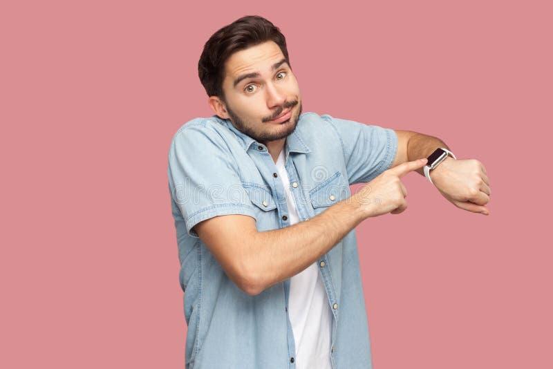 Portret van de droevige knappe gebaarde jonge mens in blauwe toevallige stijloverhemd status richtend en tonend zijn slim horloge stock fotografie