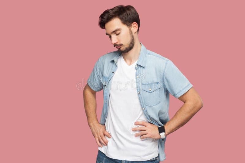 Portret van de droevige, ongelukkige of verstoorde knappe gebaarde jonge mens in blauw toevallig stijloverhemd die zich met hande stock foto's