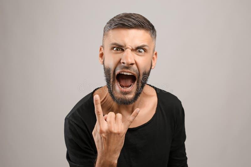 Portret van de emotionele mens op grijze achtergrond stock afbeelding