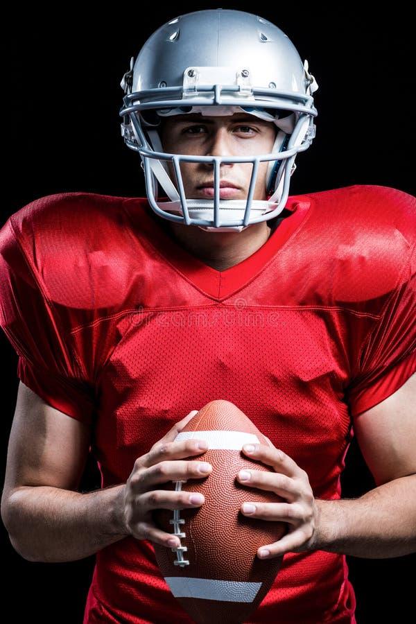 Portret van de ernstige Amerikaanse bal van de voetbalsterholding royalty-vrije stock fotografie