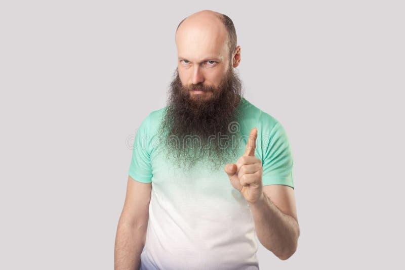 Portret van de ernstige bazige midden oude kale mens met lange baard in lichtgroene t-shirt die zich met waarschuwend gebaar bevi royalty-vrije stock afbeeldingen