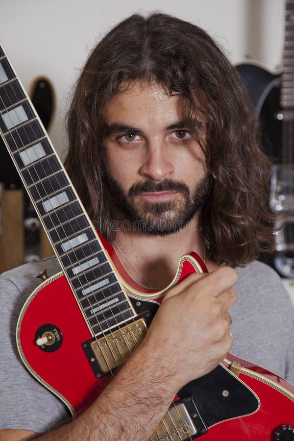 Portret van de ernstige jonge gitaar van de musicusholding stock afbeelding