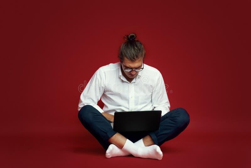 Portret van de ernstige jonge mens die in wit overhemd laptop computer bekijken terwijl het zitten op die een vloer over rode ach royalty-vrije stock afbeeldingen