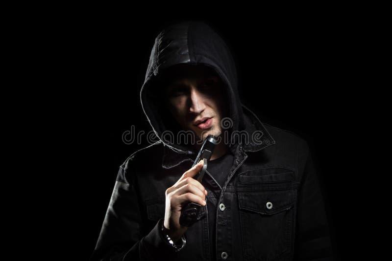 Portret van de ernstige mens met kanon in de kapzwarte royalty-vrije stock foto