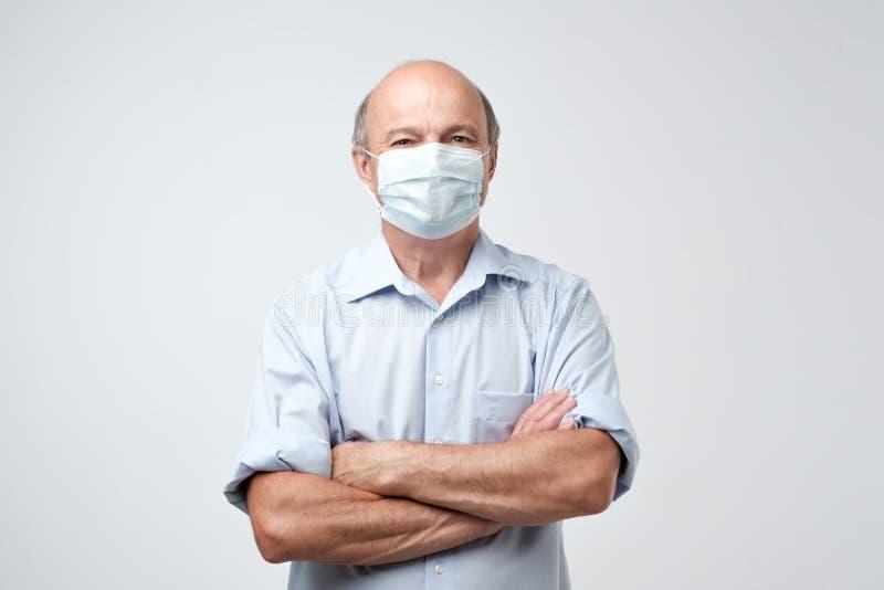 Portret van de ernstige mens in speciaal doktersmasker Hij kijkt ernstig Rijpe ervaren arts stock afbeelding