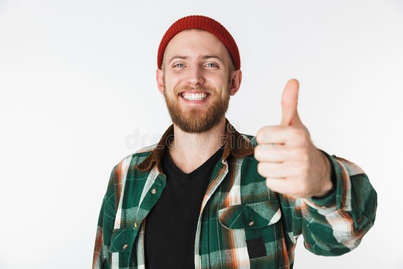 Portret van de Europese gebaarde mens die hoed en plaidoverhemd dragen die duim tonen, terwijl status geïsoleerd over witte achte royalty-vrije stock foto