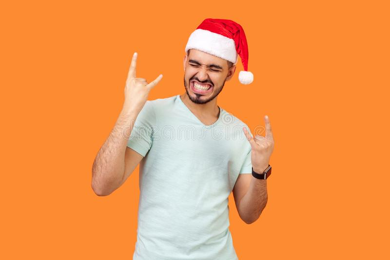 Portret van de extreem gelukkige, bebaarde jonge man in de kersthoed en het portret wit T-shirt dat met gesloten ogen staat, met  stock afbeeldingen